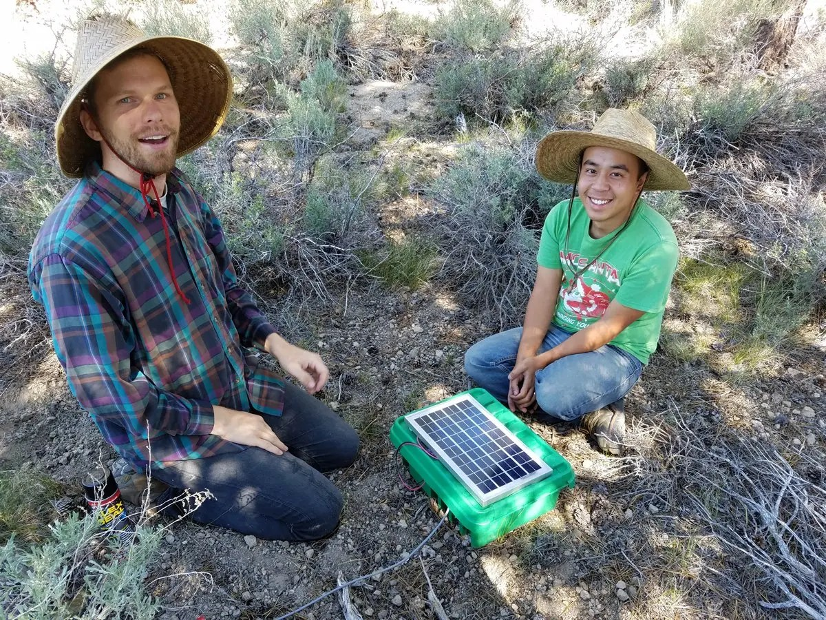 Two young men, graduate students Daniel Hastings and Justin Luong, kneel in a sagebrush field by a small plastic box with a solar panel on the top designed to collect soil moisture data.