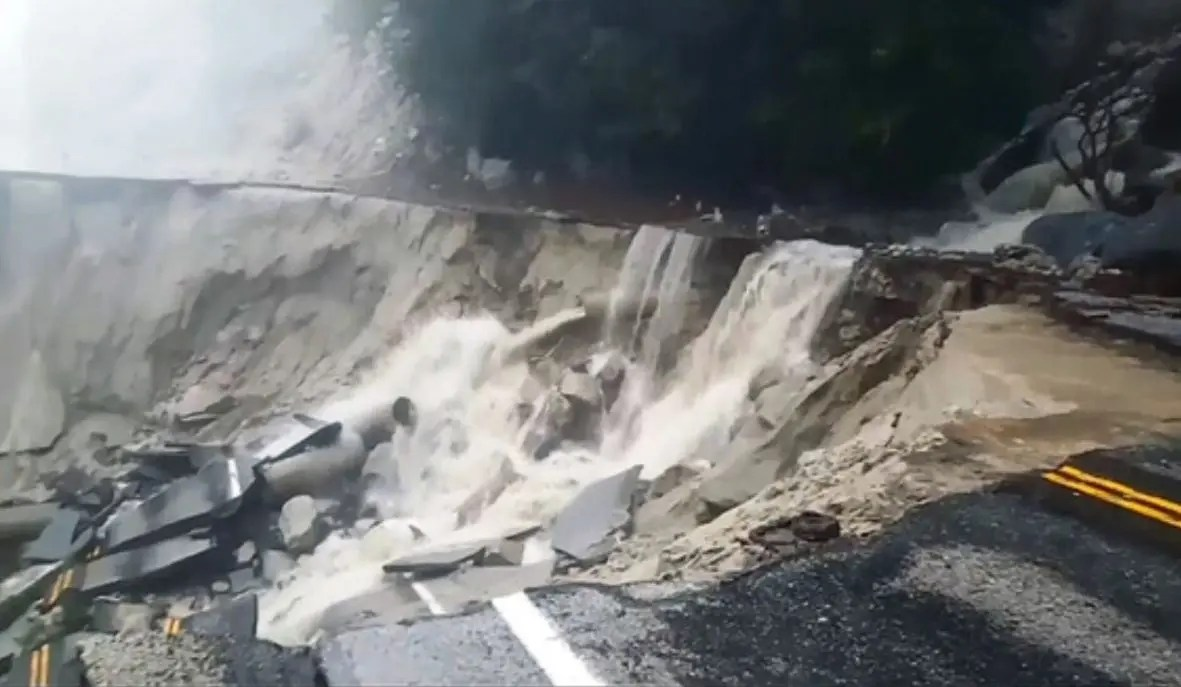 Roadway collapse obliterating both lanes with water cascading past the lip and into the sinkhole; mist in the near distance.