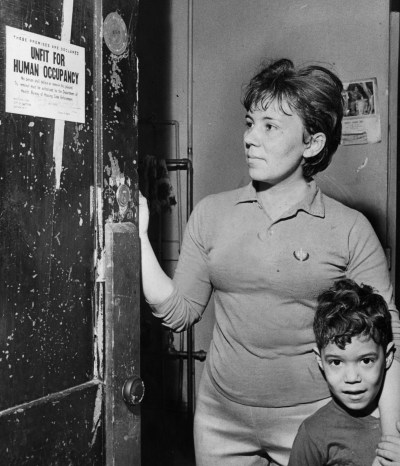 A tenant examines the distressing notification that her building is 'unfit for human occupancy,' on Feb. 2, 1970. The building was owned by Jerome Diamond, who was cited for numerous housing code violations and was issued warrants to appear in housing court.