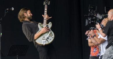 bradley cooper guitarist playing guitar filming 'A Star Is Born' in Glastonbury festival.