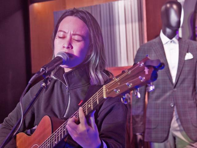 Reese Lansangan singing with her acoustic guitar