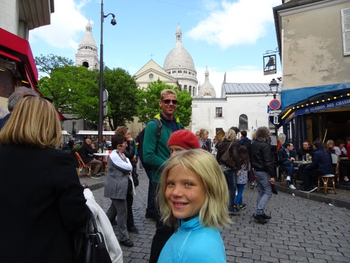 The bustling streets of Montmatre with Sacré Coeur looming