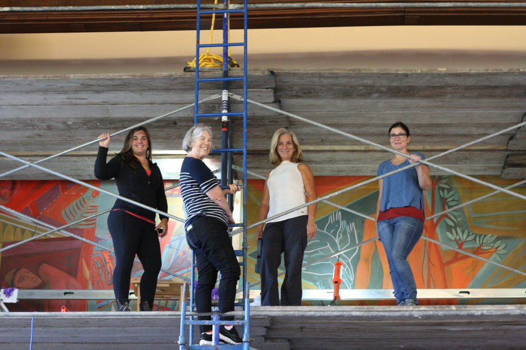 Four women on scaffolding in front of a mural