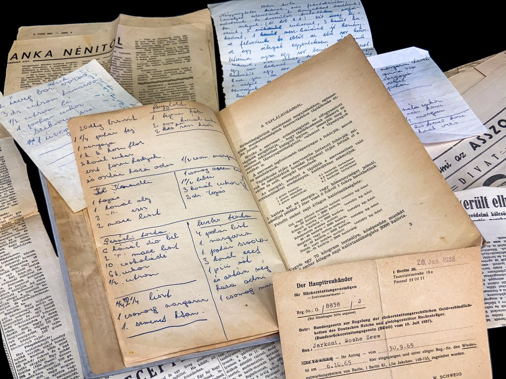 Open copy of a Hungarian cookbook surrounded by notes and newspaper clippings that were found in the book. It also features the BRüG postcard which is the subject of our post.