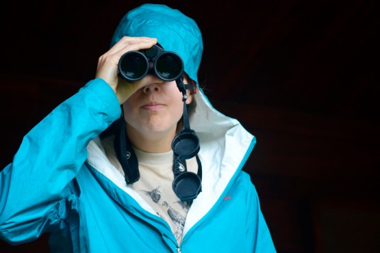 Resident naturalist Regan Fink peers through binoculars, her handy accessory for the day.