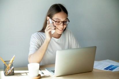 mujer-milenaria-gafas-hablando-celular-usando-laptop_1163-3976