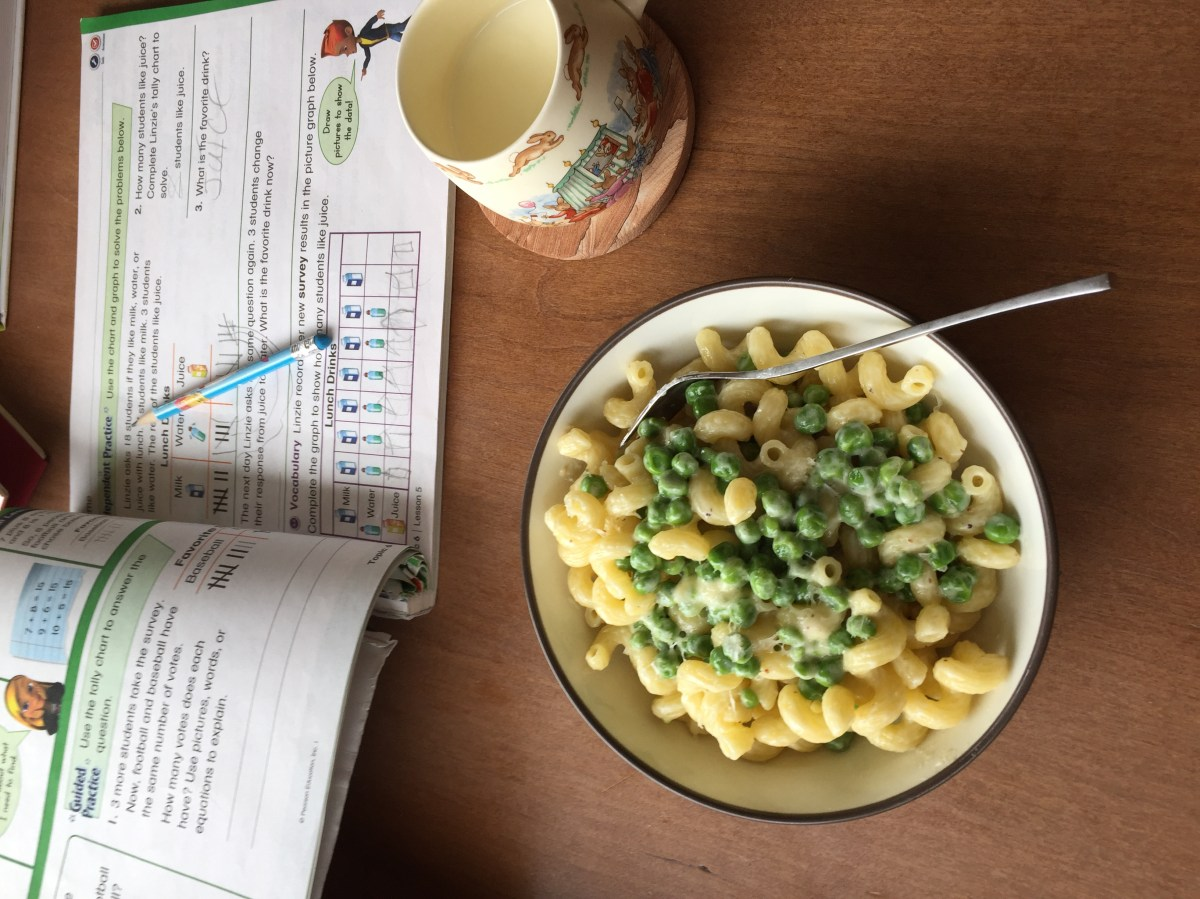 a child's homework, cup of milk, and a bowl of cavatappi alfredo and peas