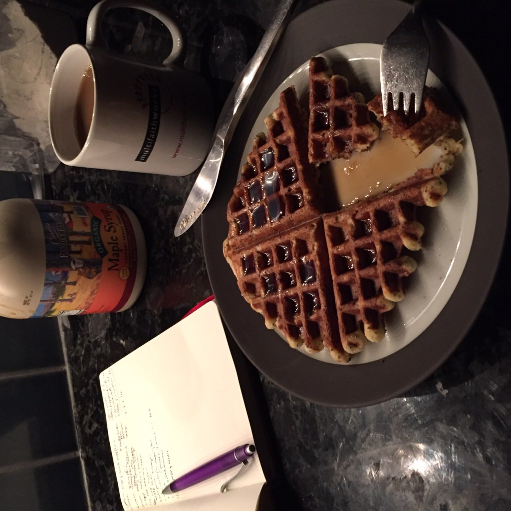 An orange poppy seed waffle on a plate with a fork and knife and syrup next to a coffee cup and a small notebook and pen