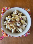 a small bowl of bacon cheddar popcorn on a colorful potholder