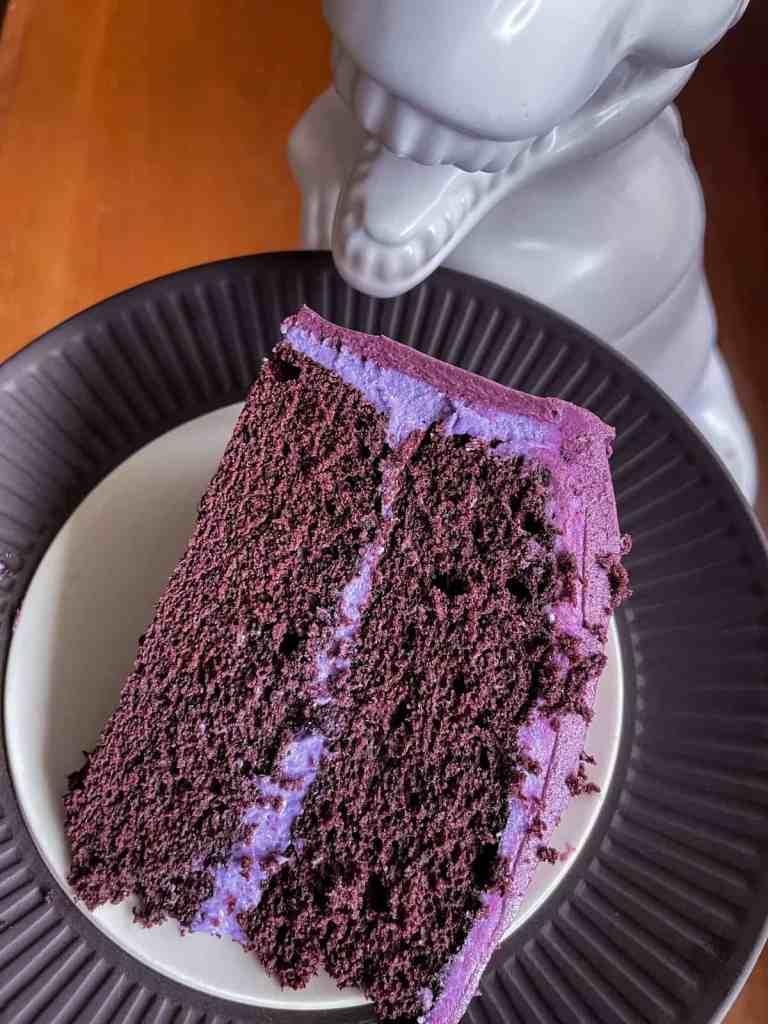 Sue the T rex eating a slice of purple velvet cake