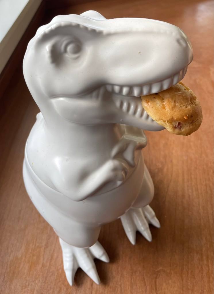 A Tyrannosaurs rex cookie jar with a cheese puff in its mouth