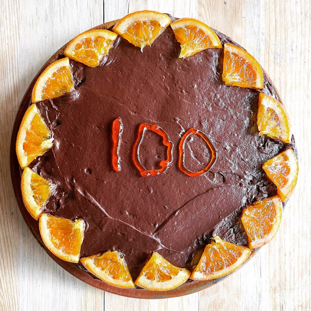 a chocolate orange cake decorated with candied orange and the number 100