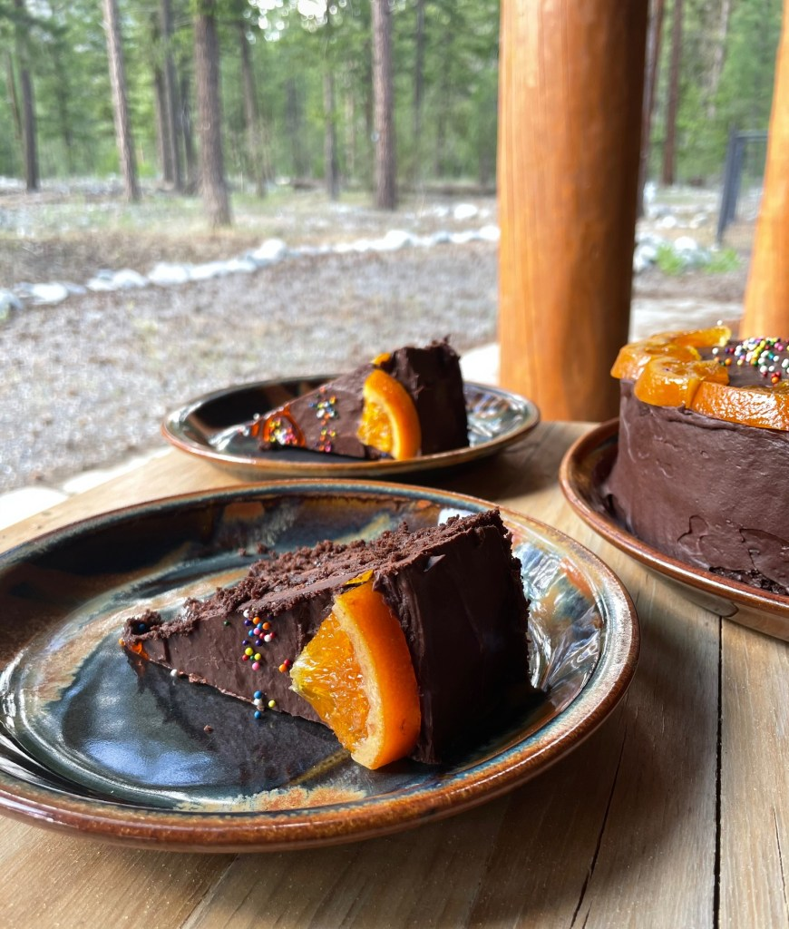 slices of chocolate orange cake on plates on a table overlooking a wooded backyard