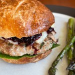 a duck burger on a bun with lettuce, cheese, and cherry ketchup on a plate with asparagus spears