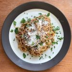 a plate with angel hair pasta and fig bacon jam and topped with Parmesan and parsley