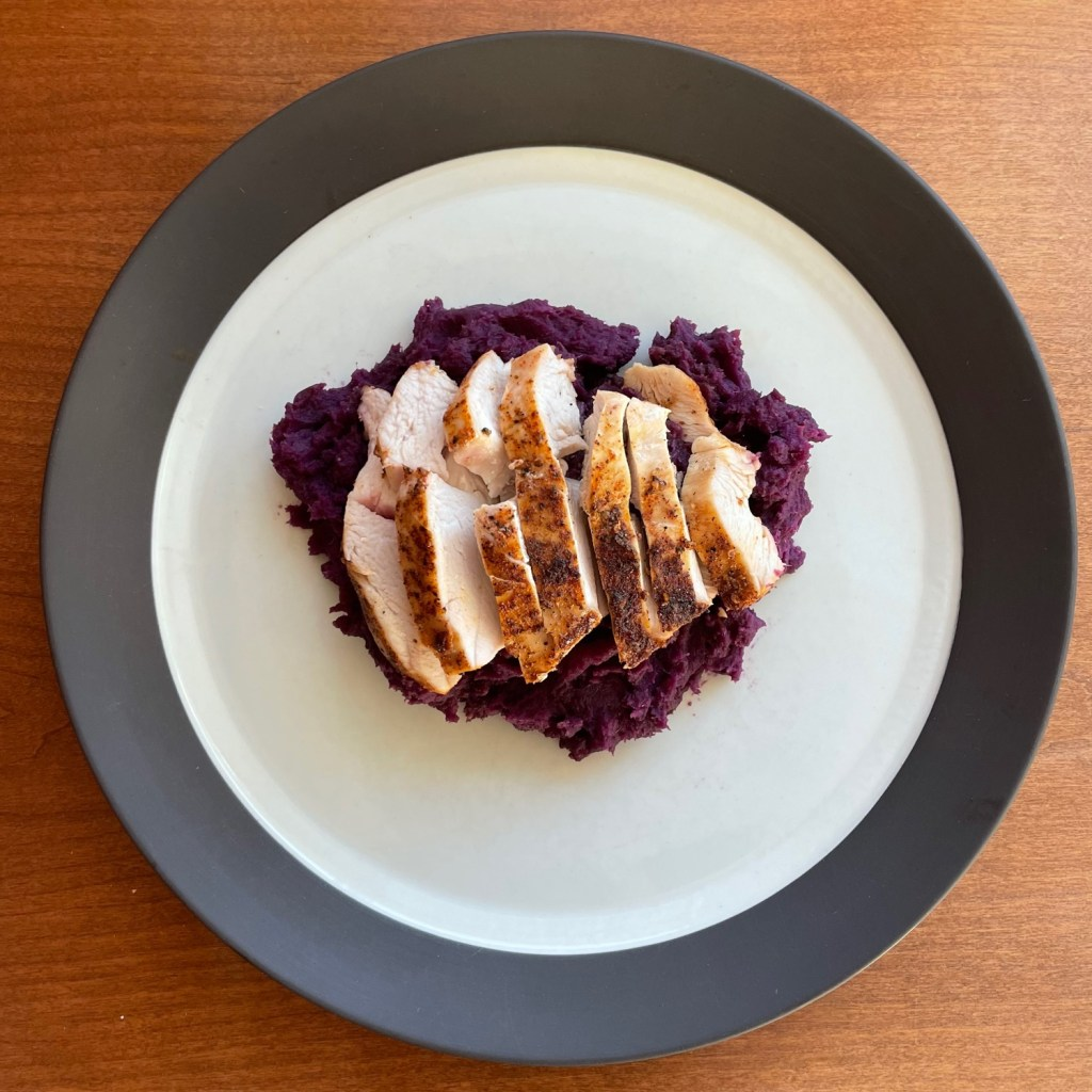 a dinner plate with sliced chicken atop purple mashed sweet potato