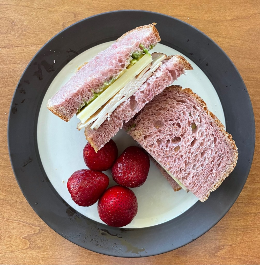 a turkey,cheese, and avocado sandwich on pink bread with 4 strawberries on a plate