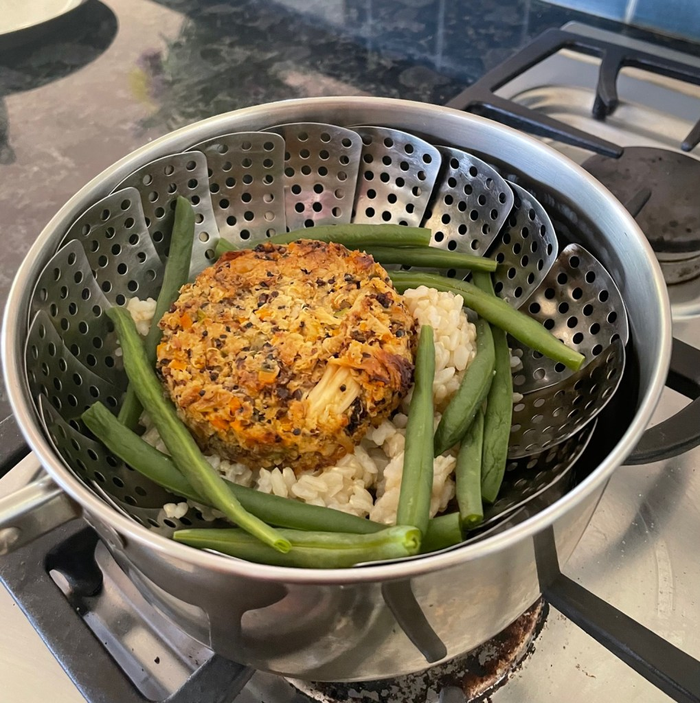 a pot and steamer basket containing a baked cauliflower patty and some green beans over brown rice
