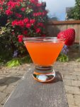 a martini glass with strawbery gimlet and garnished with a strawberry on a chair in a garden