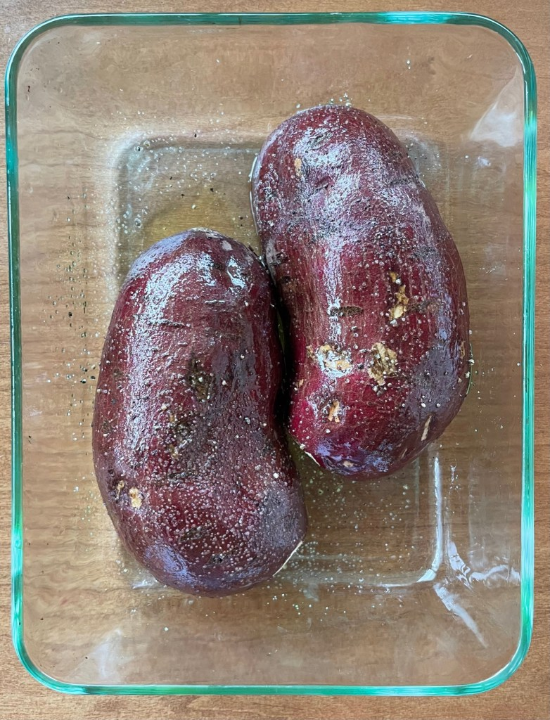 two halves of a purple sweet potato face down in a pyrex baking dish