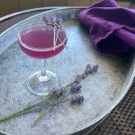 a purple cocktail on a tray with a purple napkin and several lavender sprigs