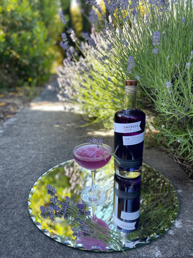 An Earl Grey and lavender Empress gin cocktail on a tray with a bottle of Empress 1908 gin and lavender sprigs, set on a path amongst a lavender bush