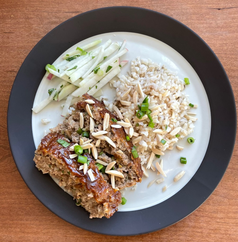 A plate with two slices of duck meatloaf, brown rice, and kohlrabi salad, garnished with sliced green onions and almond slivers
