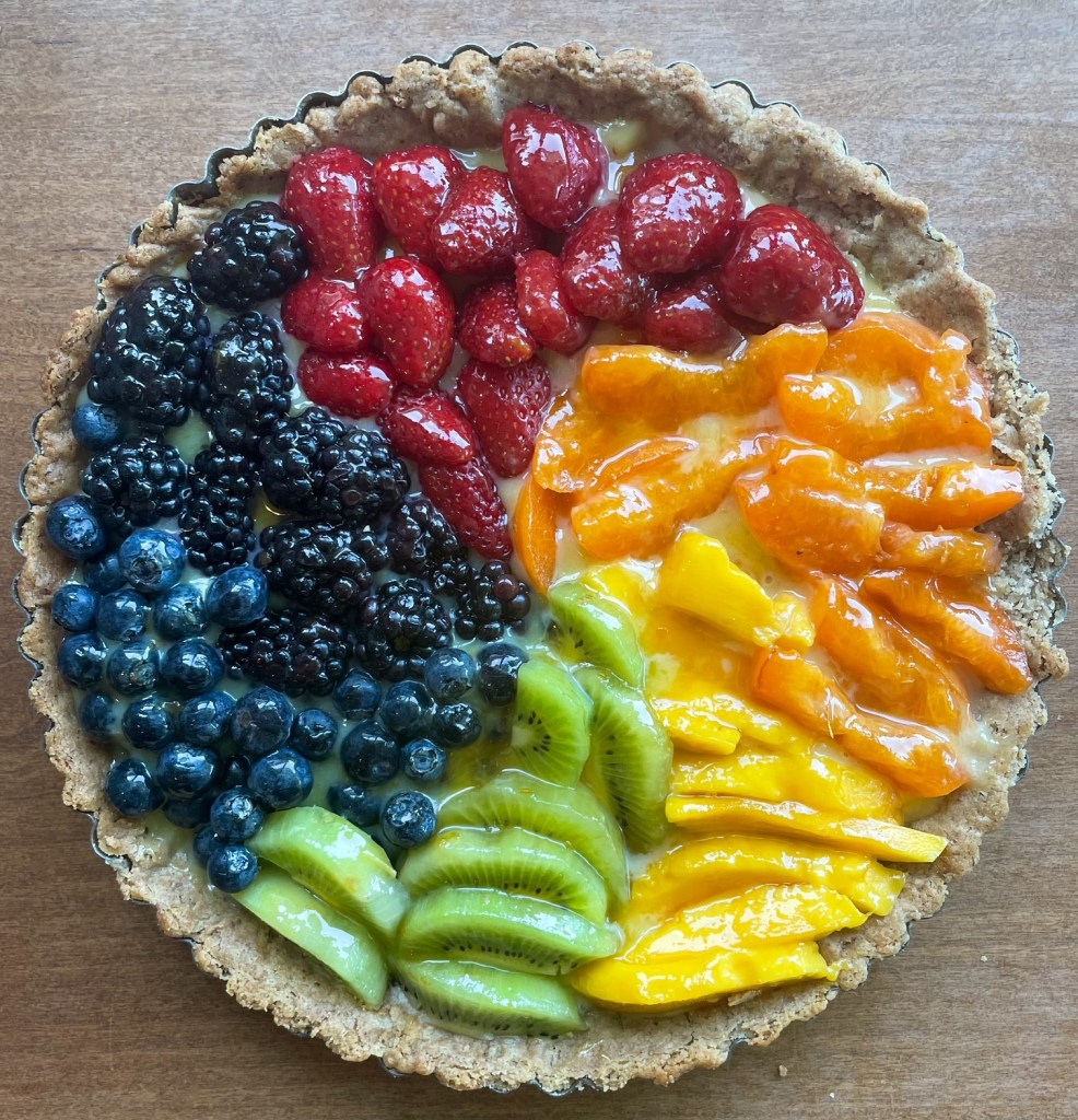 A glazed rainbow fruit tart with strawberries, apricot, mango, kiwi, blueberries, and blackberries arranged in a spiral pattern