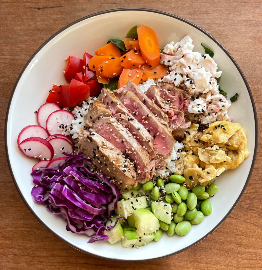 A rainbow poke bowl with sliced seared tuna, sushi crab salad, japanese scrambled eggs, and a rainbow colored array of vegetables