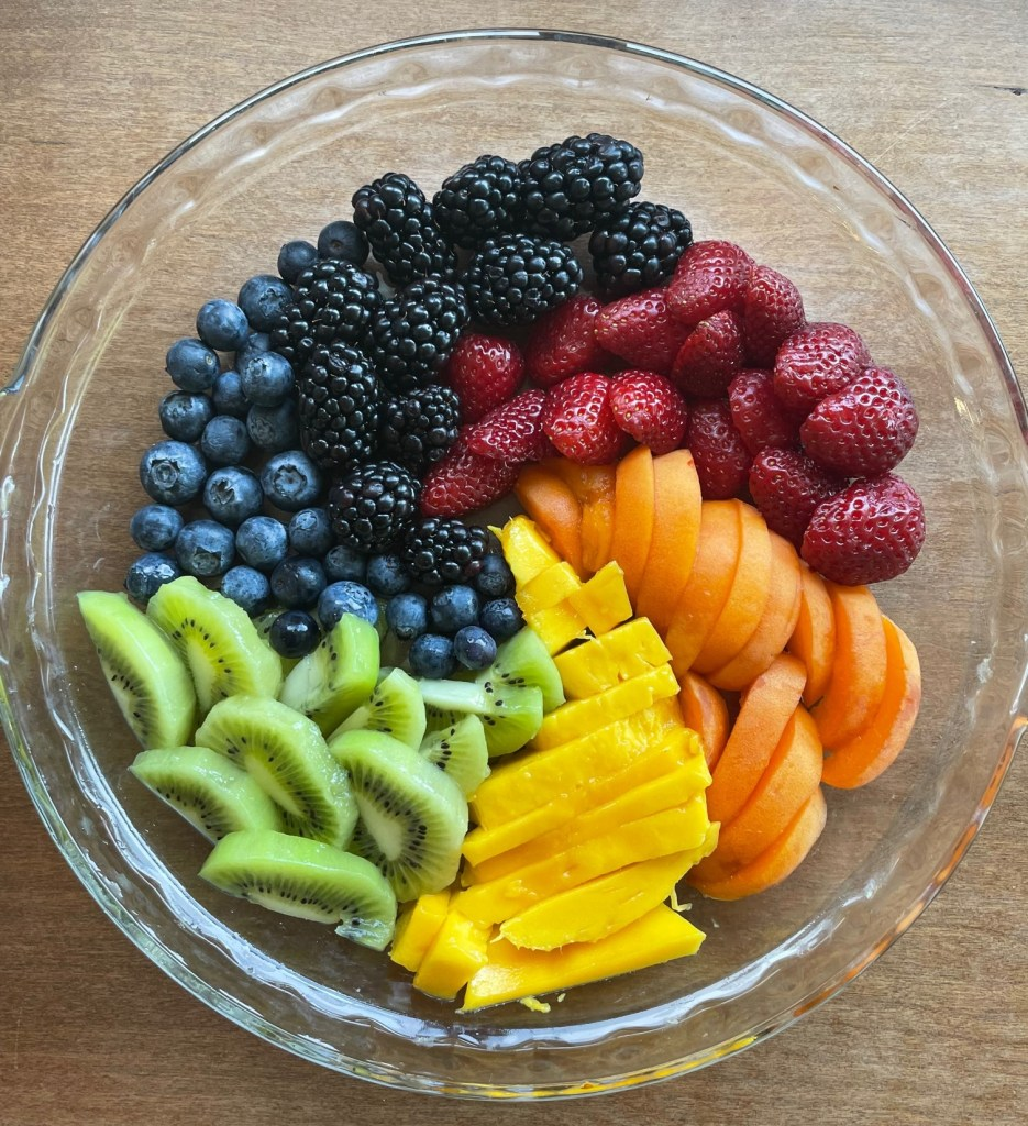 Staging of the rainbow fruit tart with strawberries, apricot, mango, kiwi, blueberries, and blackberries arranged in a glass pie pan