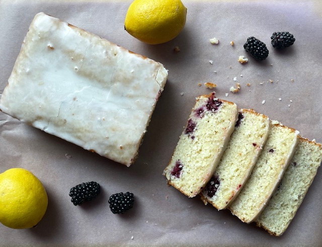 a loaf of blackberry lemon bread sliced into four slices and surrounded by four blackberries and two lemons