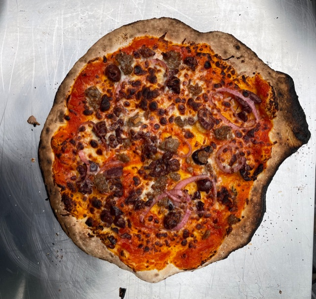 an overcooked pizza with sausage and red onions