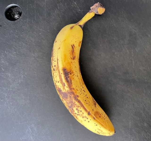 one very ripe banana on a cutting board