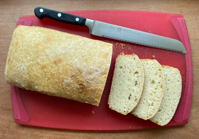 a loaf of sourdough bread, three slices, and a bread knife