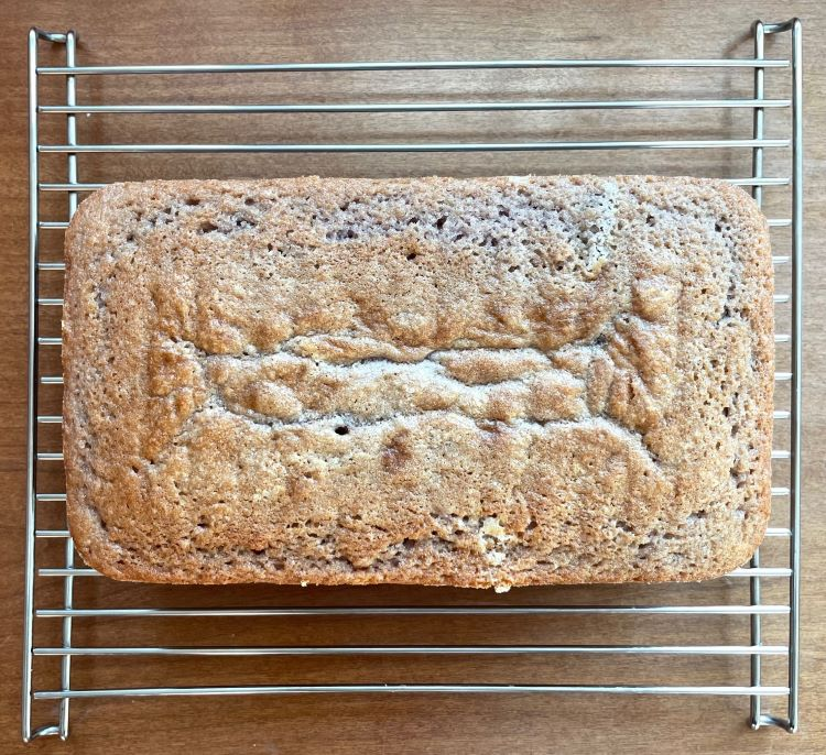 the baked but unglazed summer raspberry cake on a cooling rack