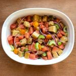 a serving bowl containing watermelon panzanella made with sourdough croutons