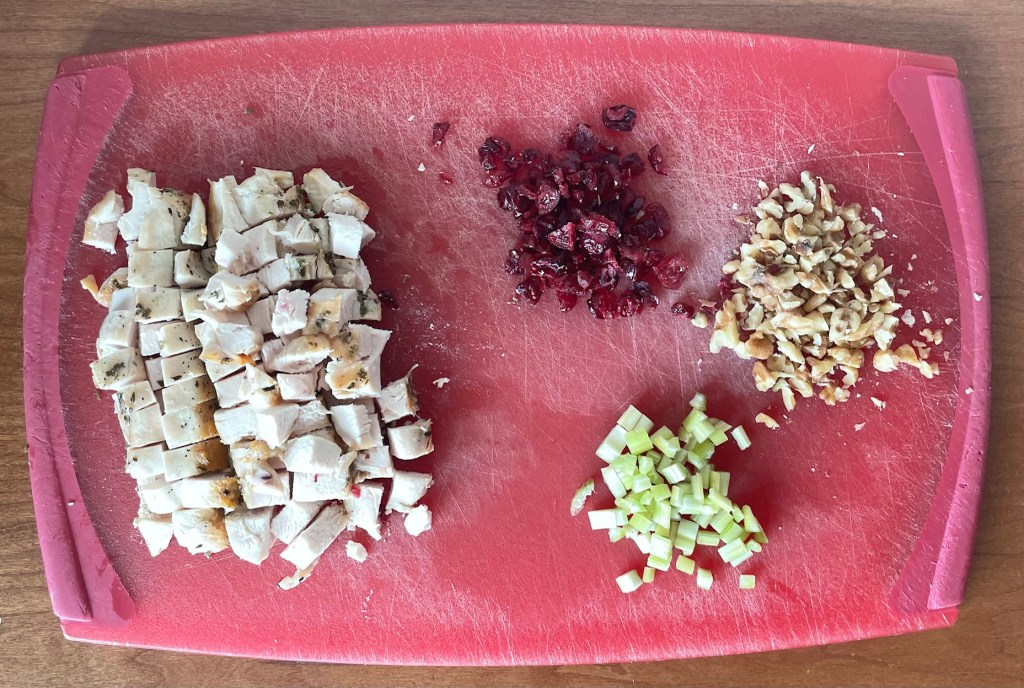 a cutting board with cubed cooked chicken, chopped dried cranberries, walnuts, and celery