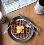 a plate with a nutella waffle, banana slices, fork and knife, and spoonful of nutella