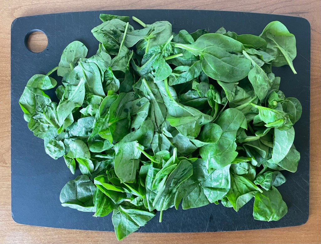 a cutting board covered with spinach