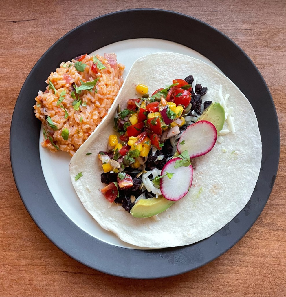 a dinner plate with a bean taco with mango pico de gallo and some Mexican rice