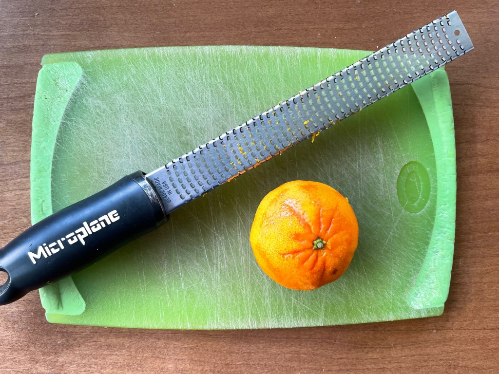an orange and microplane zester on a cutting board