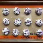 a baking sheet filled with ube crinkle cookies