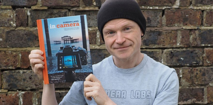 "Gordon Laing holding a copy of his book ""In Camera"""