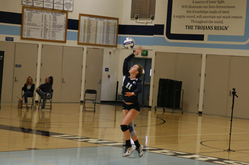 Bella Oldham (Sr.) soars into the air and slams the ball across the net, starting the play. (M.Olney)