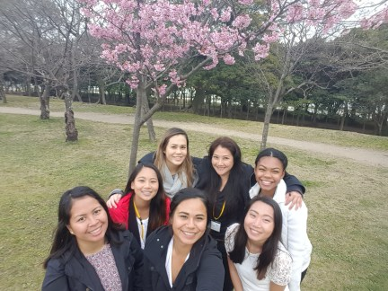The girls taking a memorable picture in front of the plum blossoms.