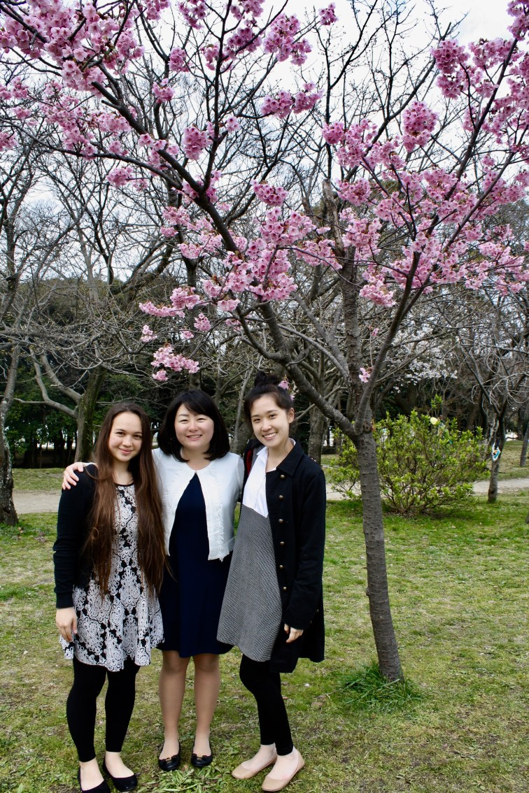 TOMODACHI Scholars smile in front of the few blossoming ume trees in Maizuru Park