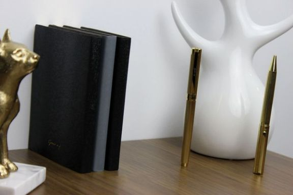 blue and black travel journal with gold pen