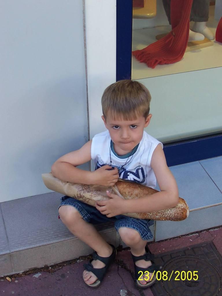 sad looking boy with bread