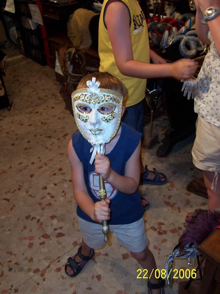 a boy with aVenitian face mask