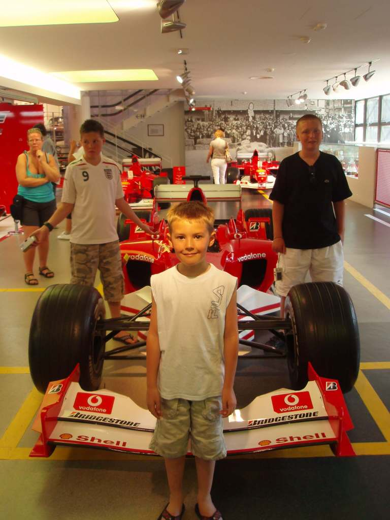 three boys with an Ferrari F1 car